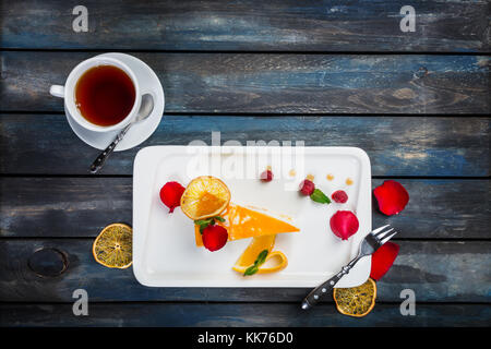 Orange cake with a cup of tea fresh raspberries on a white plate with rose petals. Top view. Beautiful wooden background. - Stock Photo