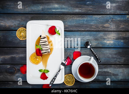 Slice of Cheesecake with a cup of tea on a white plate with rose petals. Top view. Beautiful wooden background. - Stock Photo