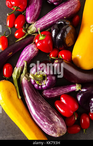 Small eggplant, yellow zucchini, tomatoes and purple pepper. Dark background. Vegetarian food from the village - Stock Photo