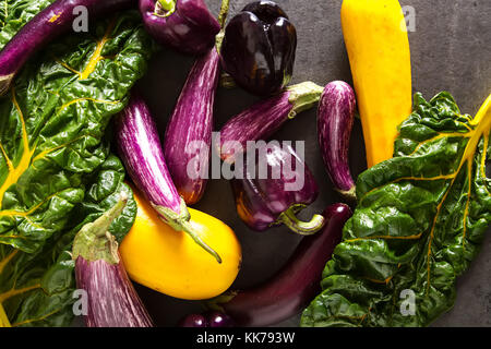 Small eggplant, yellow zucchini, chard and purple pepper. Dark background. Vegetarian food from the village - Stock Photo