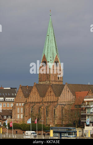 Bremen, Germany - November 23rd, 2017 - Historic St. Martin's church with tall spire and rain clouds in the background - Stock Photo