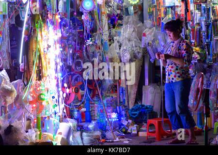Stallholder in Phnom Penh with electrical goods - Stock Photo
