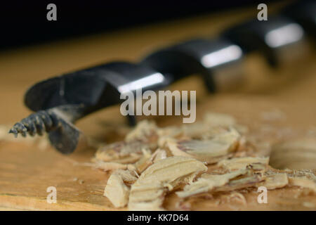 Shavings and wood drill bit on wooden board as woodworking background image. Selective focus - Stock Photo