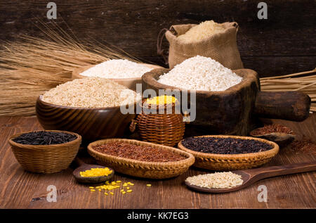 different varieties of rice in a wooden bowl on a background of dark wood - Stock Photo