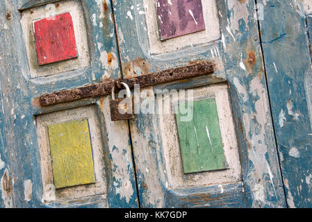 Brightly coloured flaky pain in blue, yellow, red, purple and green on old window shutters secured with a rusting - Stock Photo