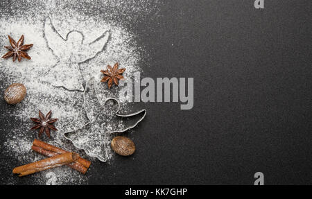 Baking christmas cookies- cookie cutters,cinnamon,anise, hazelnuts on black background - Stock Photo