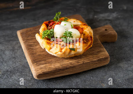 Pie in the oriental style. Filo pastry with tomato and mozzarella. Dark background. Vegetarian food - Stock Photo