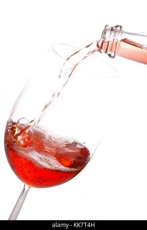 Pouring rose wine into a glass isolated on white background. - Stock Photo