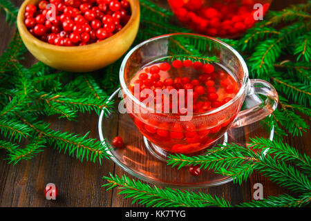 Hot tea from cranberries in a glass cup surrounded by fir branches on a wooden table - Stock Photo