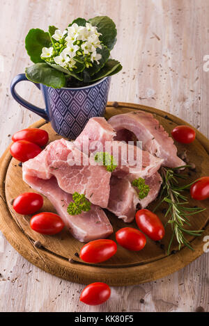 Vertical photo with few pork steaks. Raw meat is placed on vintage wooden board with red tomatoes and herbs like - Stock Photo