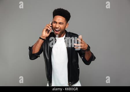 Close-up photo of angry young african man screaming while talking on smartphone, isolated on gray background - Stock Photo