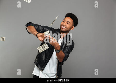Funny afro american rich man scattering dollars banknotes, isolated over gray background - Stock Photo