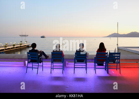 Four Tourists Enjoy the Sunset on the Boulevard de la Croisette, Cannes, at Dusk, with Dramatic Colour Street Lighting, French Riviera, france