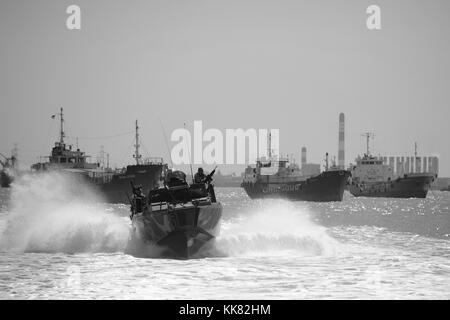 Sailors assigned to Coastal Riverine Squadron CRS 3 transit aboard a riverine command boat to Surabaya, Indonesia - Stock Photo