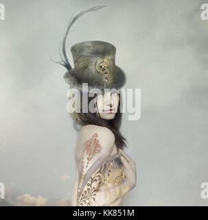 Beautiful artistic portrait of an extravagant lady in an eighteen century style and cylinder with clouds in the - Stock Photo