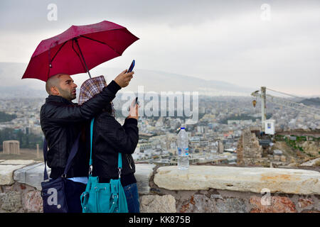 Couple with umbrellas in rain with mobile phones taking photos overlooking Athens from the Acropolis - Stock Photo