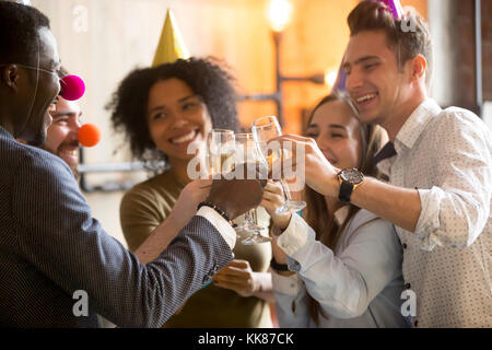 Happy black and white friends clinking glasses celebrating party - Stock Photo