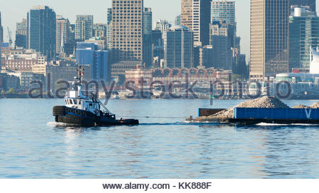 A tug boat towing a barge of gravel along Burrard Inlet in downtown Vancouver, BC. - Stock Photo
