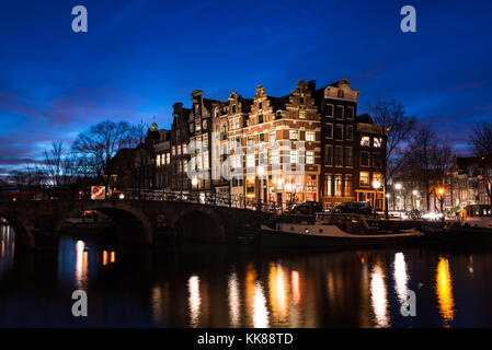 Typical Amsterdam canal houses in historic architecture along the canals a bridge over the water, illuminated at - Stock Photo
