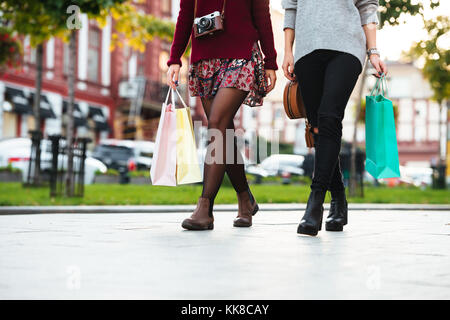 Cropped image of two young girls walking on a city street and holding shopping bags - Stock Photo