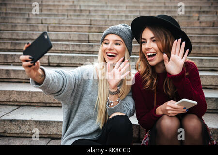 Portrait of two smiling happy girls taking a selfie while sitting on a staircase and waving hands outdoors - Stock Photo