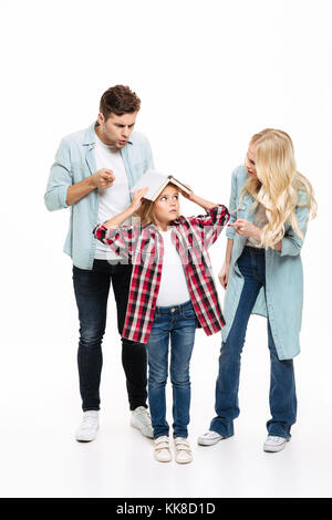 Full length portrait of a family having and argument with a child standing with a book isolated over white background - Stock Photo
