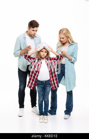 Full length portrait of a family having and argument with a child standing and holding a book isolated over white - Stock Photo