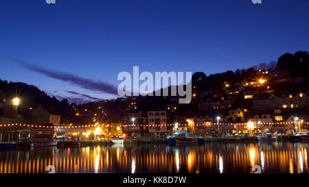 Lights and boats on the edge of the harbour, on a winter evening - Stock Photo