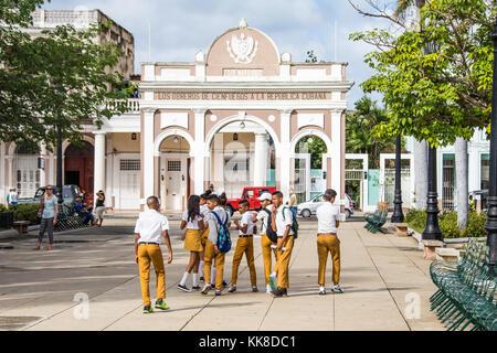 School children in uniforms and Triumphal arch Arco de Triunfo and Parque Jose Marti in Cienfuegos, Cuba, Caribbean - Stock Photo