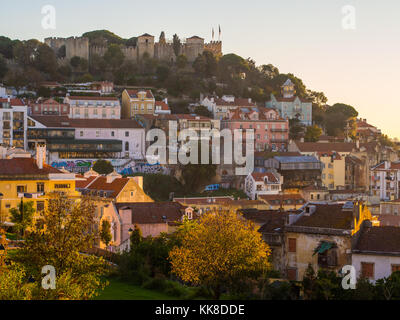 Soa Jorge Castle in Lisbon, Portugal, with the sourrounding architecture, at sunset. - Stock Photo