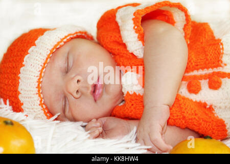 Cute peaceful sleeping newborn baby dressed in a knitted orange costume with oranges around of him on white blanket. - Stock Photo