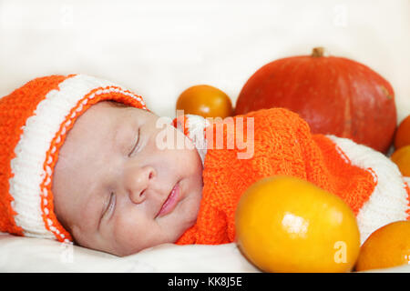 Cute sleeping smiling  newborn baby dressed  in a knitted orange costume with pumpkin and oranges background. Autumn - Stock Photo