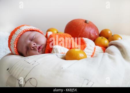 Cute sleeping newborn baby  in a knitted pumpkin or orange costume on pumpkin and oranges background. Autumn halloween - Stock Photo