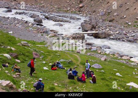 Trekkers resting near a river bank. Himachal Pradesh, Northern India - Stock Photo