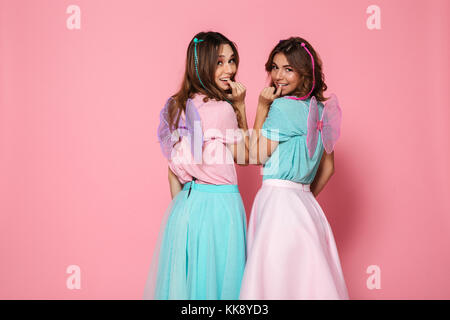 Two pretty smiling girls dressed like fairies with wings looking at camera over shoulder isolated over pink background - Stock Photo