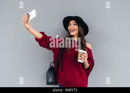 Portrait of a smiling young asian girl dressed in hat and sweater holding coffee cup while taking a selfie outdoors - Stock Photo