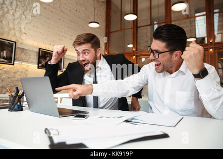Two happy entrepreneurs looking at laptop screen celebrating success in office - Stock Photo