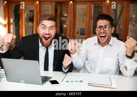 Two happy business partners with raised hands looking at camera while celebrating success in office - Stock Photo