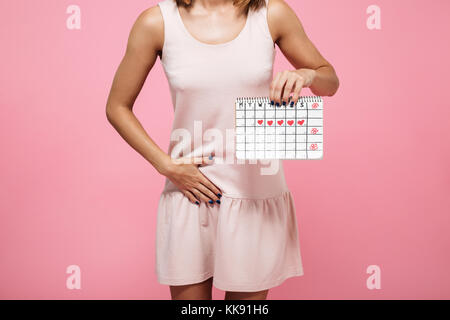 Cropped image of a young woman in dress holding periods calendar and touching her belly isolated over pink background - Stock Photo