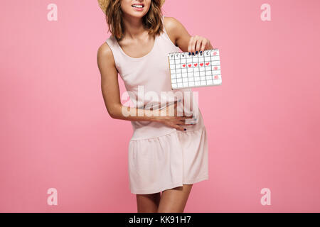 Cropped image of a young woman in dress suffering from belly pain and showing her periods calendar isolated over - Stock Photo