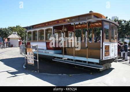 A photograph of a cable car on a turntable, a group of people are waiting to board the cable car, turntables are - Stock Photo