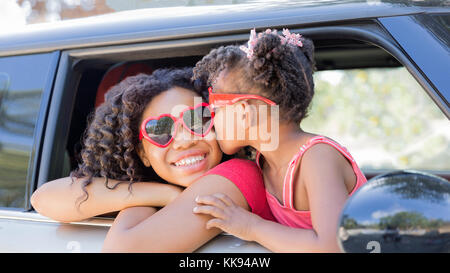 Summer fun! Happy girls or sisters with heart shaped sunglasses in car window. Younger girl kisses older girl on - Stock Photo