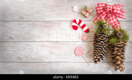 Festive Winter holiday wood background with ornaments, knitted ornament, candy and pine-cones. - Stock Photo