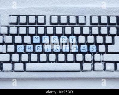 computer keyboard covered with white snow with inscription merry christmas on buttons - Stock Photo