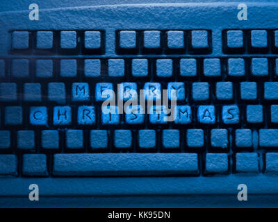 computer keyboard with lettering merry christmas on buttons covered with snow illuminated by blue neon light - Stock Photo