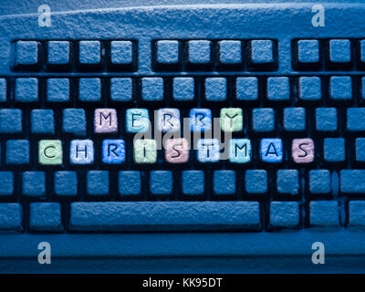 computer keyboard with multicolored text merry christmas on buttons covered with snow illuminated by blue neon light - Stock Photo