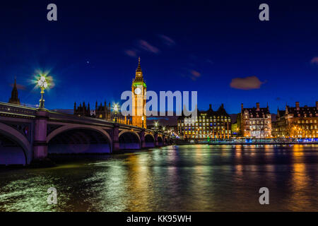 Famous landmark, Big Ben clock tower at night taken from the South side of the Thames River in central London. - Stock Photo