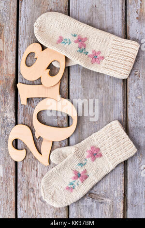 Wooden number 2018 and knitted mittens. - Stock Photo