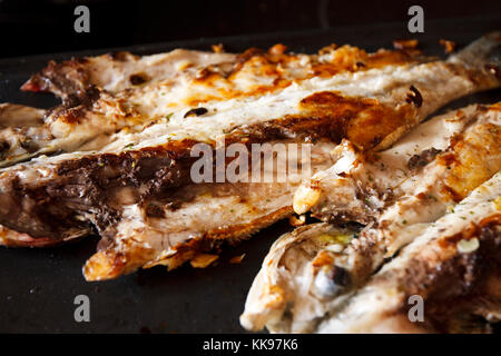 Two sea bass in half on the griddle. Low key. - Stock Photo