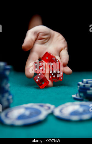 Image of man throwing red dices on table with chips in casino - Stock Photo